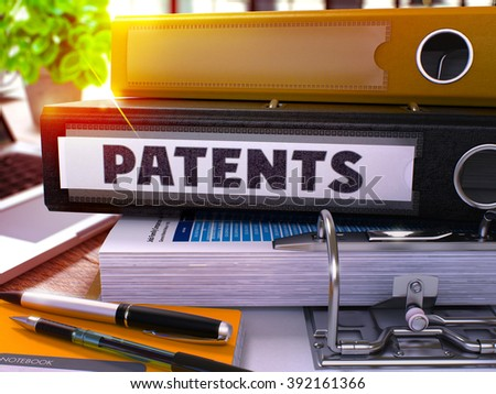 Black Office Folder with Inscription Patents on Office Desktop with Office Supplies and Modern Laptop. Patents Business Concept on Blurred Background. Patents - Toned Image. 3D. - stock photo