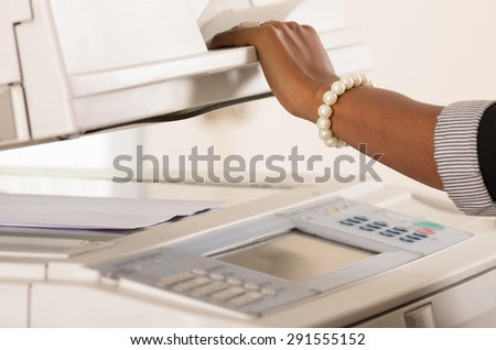 Black office womans hand lifting up lid of copy machine - stock photo