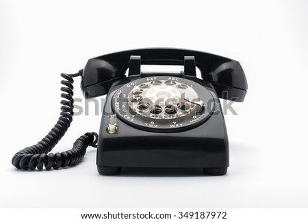 Black old telephon with rotary dial on white background - stock photo