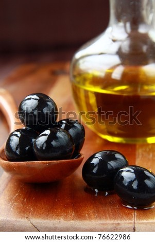 black olives and Olive Oil on an old tablel - stock photo