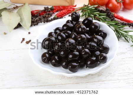 Black olives in the bowl with rosemary branch