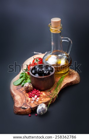 Black olives with bottle of oil on a wooden table - stock photo