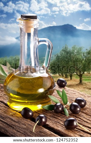 Black olives with bottle of oil on a wooden table on a background of olive garden. - stock photo