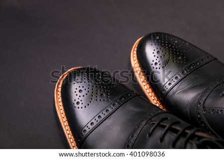 black oxford shoes with shoelace on black background closeup, top view  - stock photo
