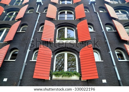 Black painted facade of traditional building with red shutters in Amsterdam, Holland  - stock photo