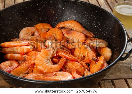 black pan with  red cooked  prawns close up  on wooden table - stock photo