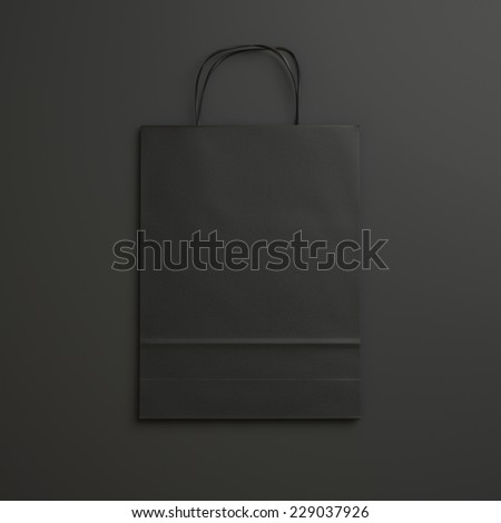 black paper bag on black background with handles - stock photo