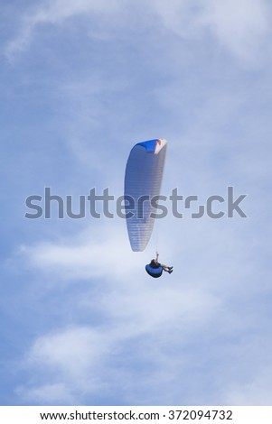 black paraglider flying in cloudy white and blue sky - stock photo
