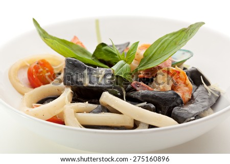 Black Pasta with Seafood and Parmesan Cheese. Garnished with Basil Leaf - stock photo
