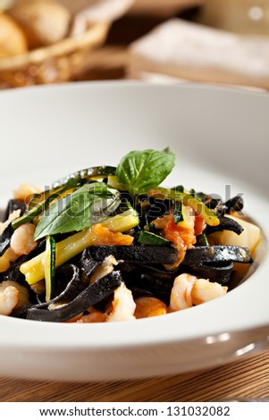 Black Pasta with Seafood and Vegetables. Garnished with Basil Leaf