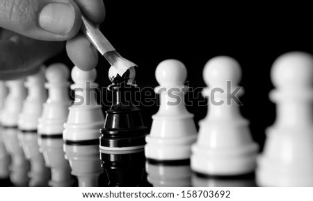 black pawn being painted white as the rest of the pawns - stock photo