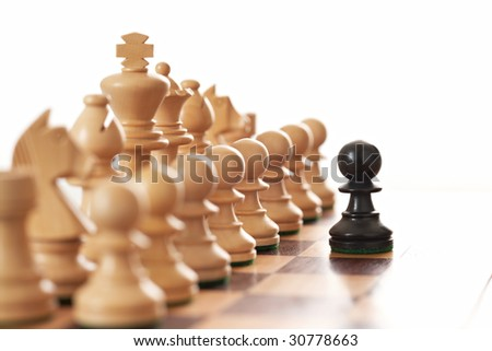 Black pawn challenging army of white chess pieces selective focus - stock photo