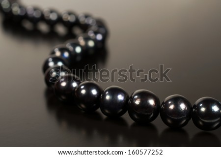 Black pearl necklace on a dark background with reflection