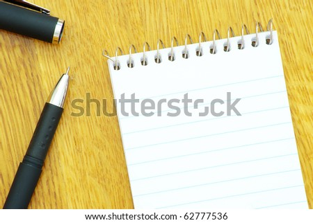 black pen and notebook in wood - stock photo