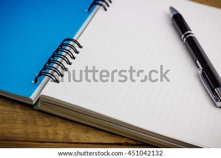 black pen on the closed notebook lying on a wooden table