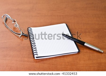 Black pen with notebook and glasses - stock photo