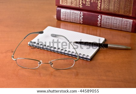Black pen with notebook and glasses on the desk - stock photo