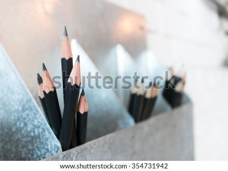 Black pencil in box. Black pencil. Pencil in box. Wooden pencil. Pencil set. Pencil concept. Black pencil collection. Sharpen pencil. Pencil and space. Black pencil at wall. - stock photo