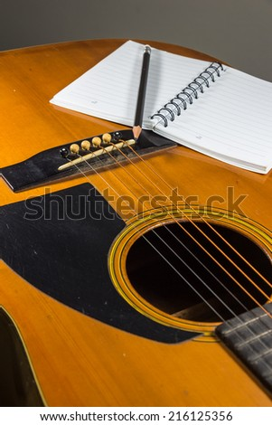 black pencil with white notebook on the guitar.