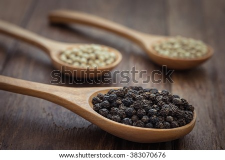 Black pepper and white pepper on wooden spoon