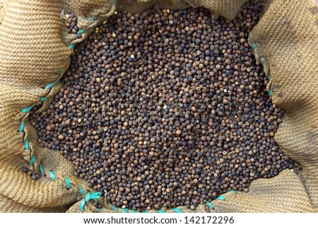 Black pepper in the big bag in indian market - stock photo