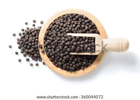 black pepper in the wooden plate, top view