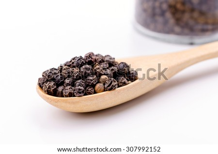 Black pepper in wooden spoon on white background. - stock photo