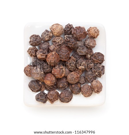 Black pepper (Piper nigrum) in a white bowl on white background. Used as a spice in cuisines all over the world. The plant is also used in medicine. - stock photo