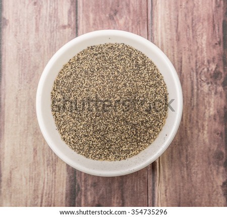 Black pepper powder in white bowl over wooden background - stock photo