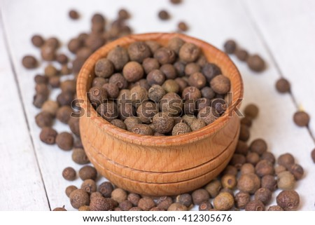 Black Peppercorns on a white table. - stock photo