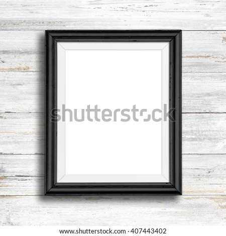 Black picture frame on white wood wall. - stock photo