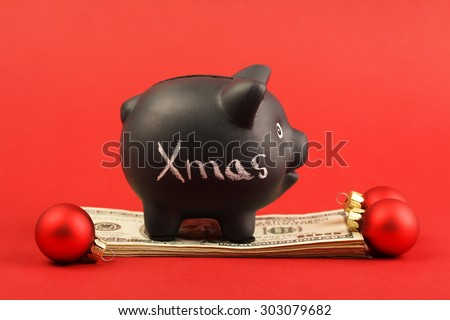 Black piggy bank with text Xmas standing on stack of money american hundred dollar bills and three red matt christmas balls on red background - stock photo