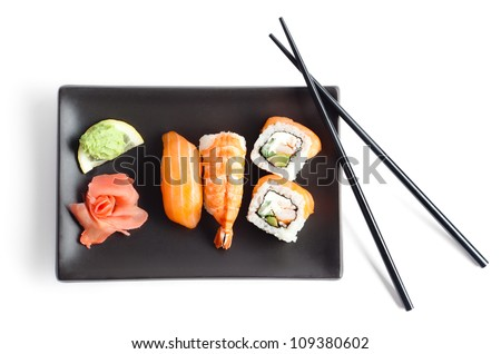 Black plate with sushi and chopsticks, isolated - stock photo