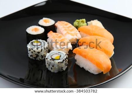 Black plate with sushi isolated on white background - stock photo