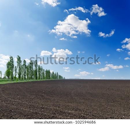 black plowed field under blue sky - stock photo
