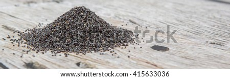 Black poppy seeds over wooden background