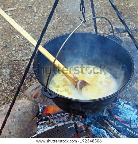 black pot on camp fire, cooking in big metallic cauldron outdoor - stock photo