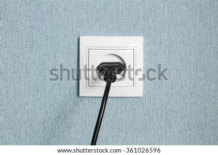 Black power plug in a socket on blue wall