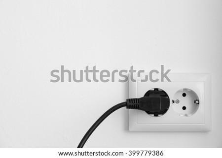 Black power plug into socket against white wall background - stock photo