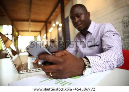 Black professional businessman in business formal attire on his mobile cell smartphone - stock photo