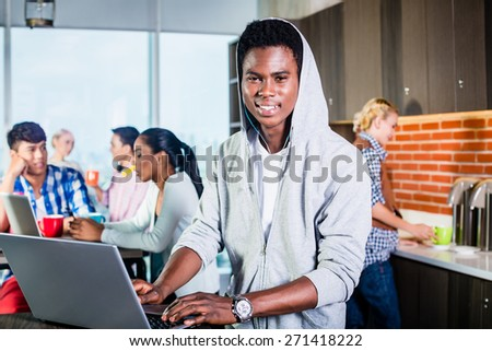Black programmer in lounge of IT start-up coding software on his laptop, colleagues in the background - stock photo