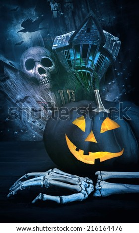 Black pumpkin with skeleton hand against eerie background - stock photo