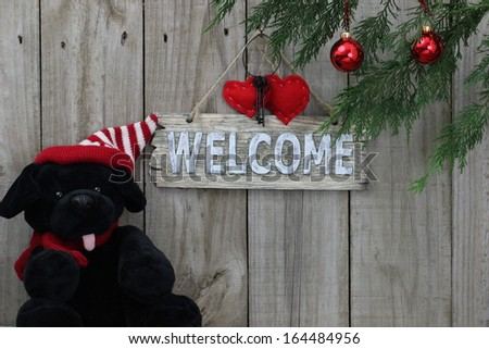 Black puppy by wood welcome sign with holiday ornaments - stock photo