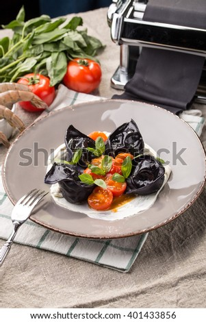 Black ravioli with shrimp and ingredients on the table - stock photo