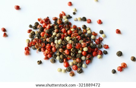 black, red, white pepper peas on white background - stock photo