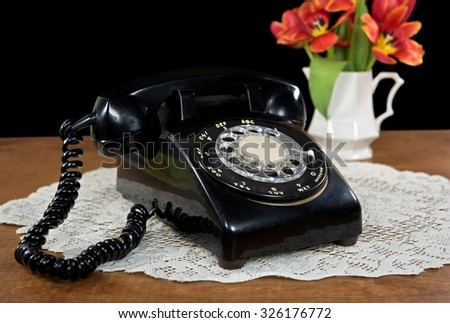 black retro telephone on lace doily with tulip bouquet in pitcher - stock photo