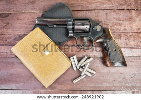 Black revolver gun and and leather bag over on wooden background. - stock photo