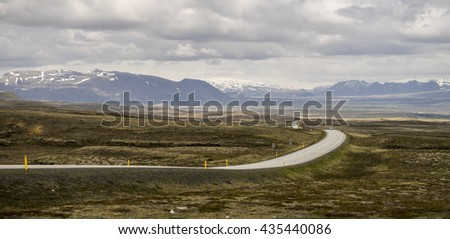 Black road leading away into horizon through the valley. Iceland.