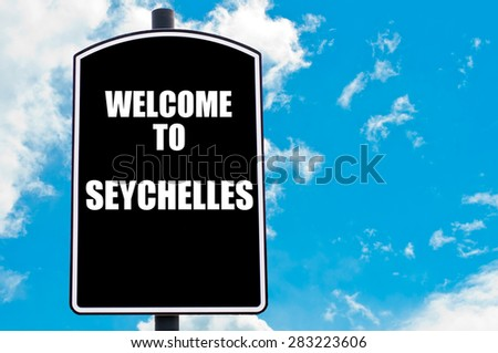 Black road sign with greeting message WELCOME TO SEYCHELLES isolated over clear blue sky background with available copy space. Travel destination concept  image