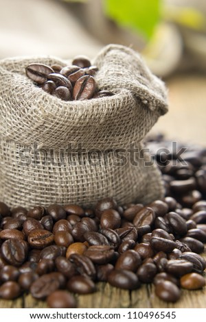 Black roasted coffee beans in a small burlap sack